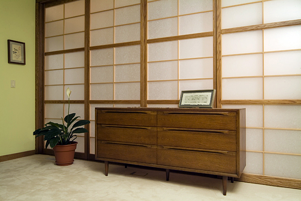 A wall of three fixed shoji screens with one sliding door  at the top of the stairs. The fixed shoji are installed with an interlock system to form a solid wall. Instead of reinforced shoji paper we used 2.0 mm Warlon Acrylic, a rigid sheet product