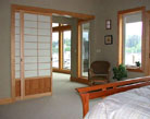 Pocket door shoji screen room dividers separate the master bedroom from the living area